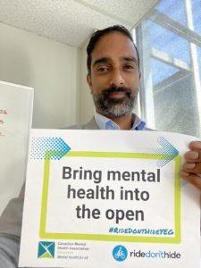 Holding sign that reads Bring mental health into the open. Promotional material for Ride Don't Hide Edmonton.
